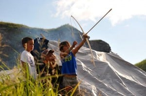 Boys learn to shoot a bow and arrow, Akhiok Petroglyph Camp, Cape Alitak.