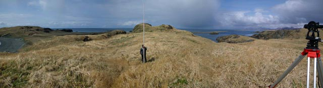 Mark Rusk and Patrick Saltonstall using a transit and stadia rod to map settlements at Cape Alitak.