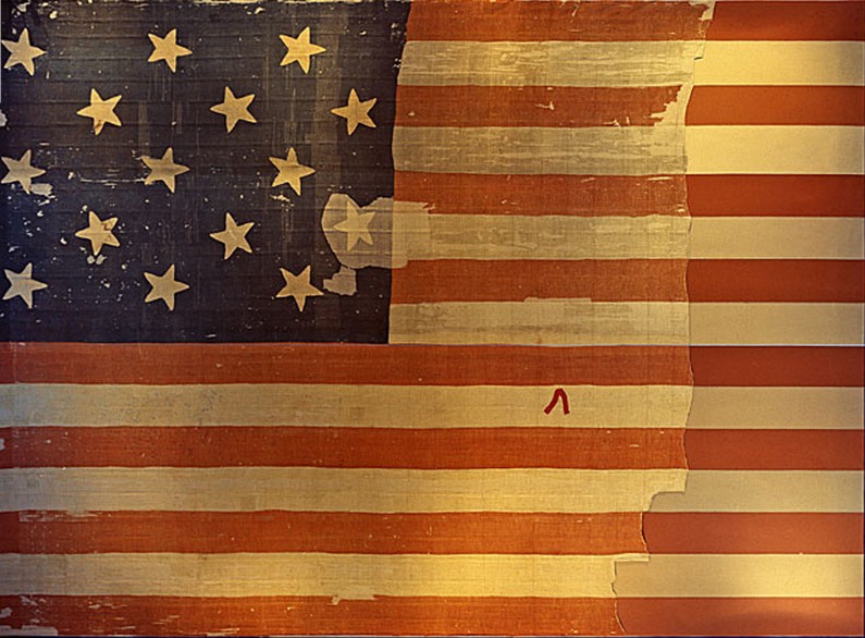 """The flag that inspired Francis Scott Key to write what would become """"The Star Spangled Banner,"""" shown on display at the Smithsonian's National Museum of History and Technology, around 1964. Many pieces were cut off the flag and given away as souvenirs early during its history. A linen backing, attached in 1914, shows the original extent of the flag. Image-Wikipedia"""