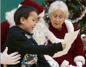 Santa and Mrs. Claus visiting a village child. Image-Department of Military Affairs