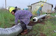 Installing water pipes in Selawik