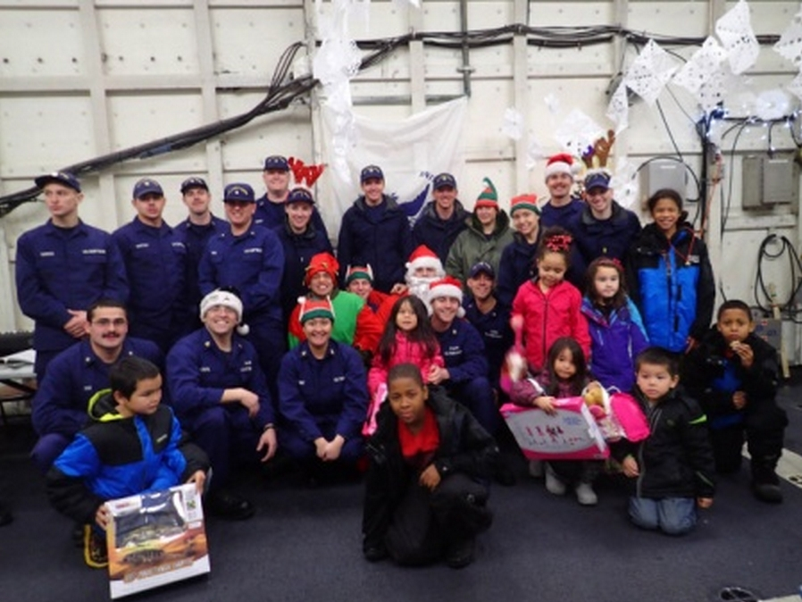 Crew members from the Coast Guard Cutter Alex Haley and Santa Claus join children from Akutan, Alaska, during a visit to the village Dec. 23, 2014. The crew of the CGC Alex Haley delivered Santa along with gifts and charitable donations to the village. (U.S. Coast Guard photo submitted by CGC Alex Haley)