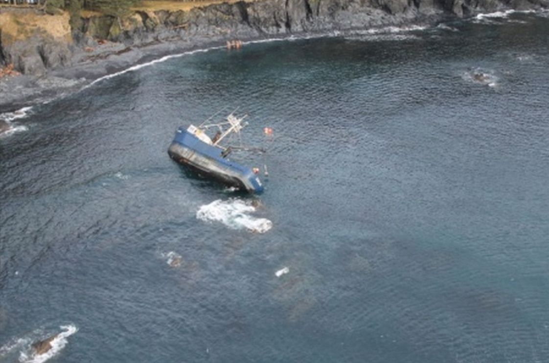 A Coast Guard Air Station Kodiak MH-60 Jayhawk helicopter crew conducts an overflight of the grounded fishing vessel Savannah Ray after reports of a diesel sheen near Kodiak Island, March 5, 2015. The Savannah Ray initially ran aground Feb. 16, 2015, with four people aboard who were rescued by an aircrew from Air Station Kodiak. (U.S. Coast Guard photo)