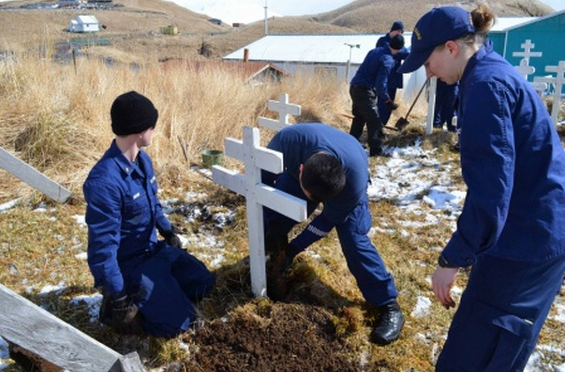 Coast Guard Cutter Alex Haley crew members place grave markers at a cemetery in Atka, Alaska, April 21, 2015. The hand-made crosses replaced those planted by the crew of the Coast Guard Cutter Storis during community outreach in 2006.