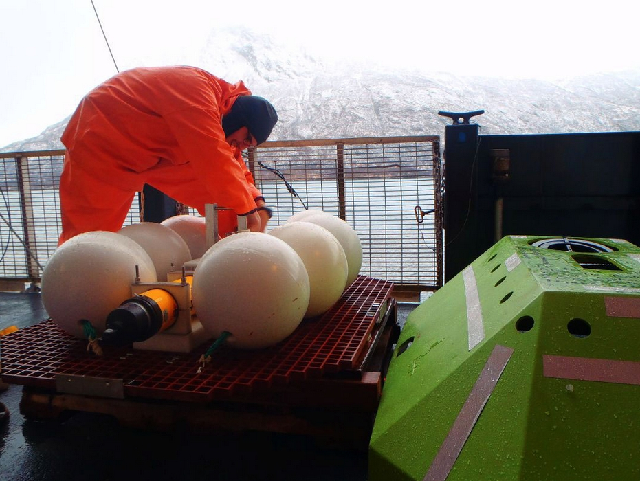 NOAA Fisheries scientist Robert Levine prepares the upward-facing sonar unit for deployment in Shelikof Straits in February of 2015. Image-NOAA