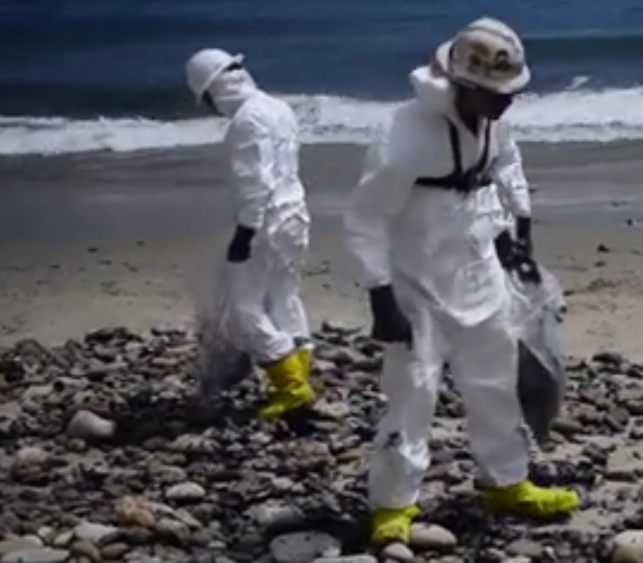 Hazmat-suited workers cleaning up tar-like crude from the Refugio State Beach. Image-USCG