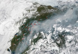 This natural-color satellite image was collected by the Moderate Resolution Imaging Spectroradiometer (MODIS) aboard the Terra satellite on June 25, 2015. Actively burning areas, detected by MODIS's thermal bands, are outlined in red.  NASA image courtesy Jeff Schmaltz, MODIS Rapid Response Team. Caption: NASA/Goddard, Lynn Jenner