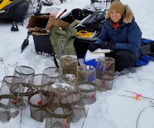 Susan Walker sits with salmon traps in the snow. Image-NOAA