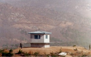 The North Korean boundary of the DMZ is clearly visible in the background. The clear area, which is on the south side of a fence, is the North Korean's minefield. The dirt is checked each day for any signs of footprints or other disturbances. Image-Public Domain