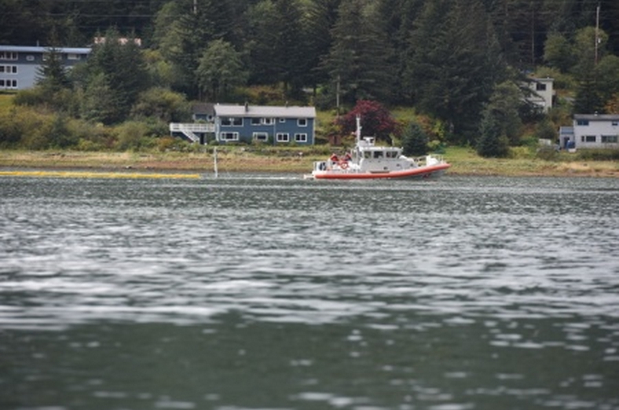Responders deploy oil containment boom around the sunken tug (All that can be seen is the mast) as it lays on the bottom in Gastineau Channel. Image-Petty Officer 2nd Class Grant DuVuyst/Coast Guard