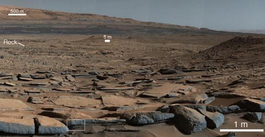 A view from the Kimberley formation looking south. The strata in the foreground dip towards the base of Mount Sharp, indicating the ancient depression that existed before the larger bulk of the mountain formed. Credit: NASA/JPL-Caltech.