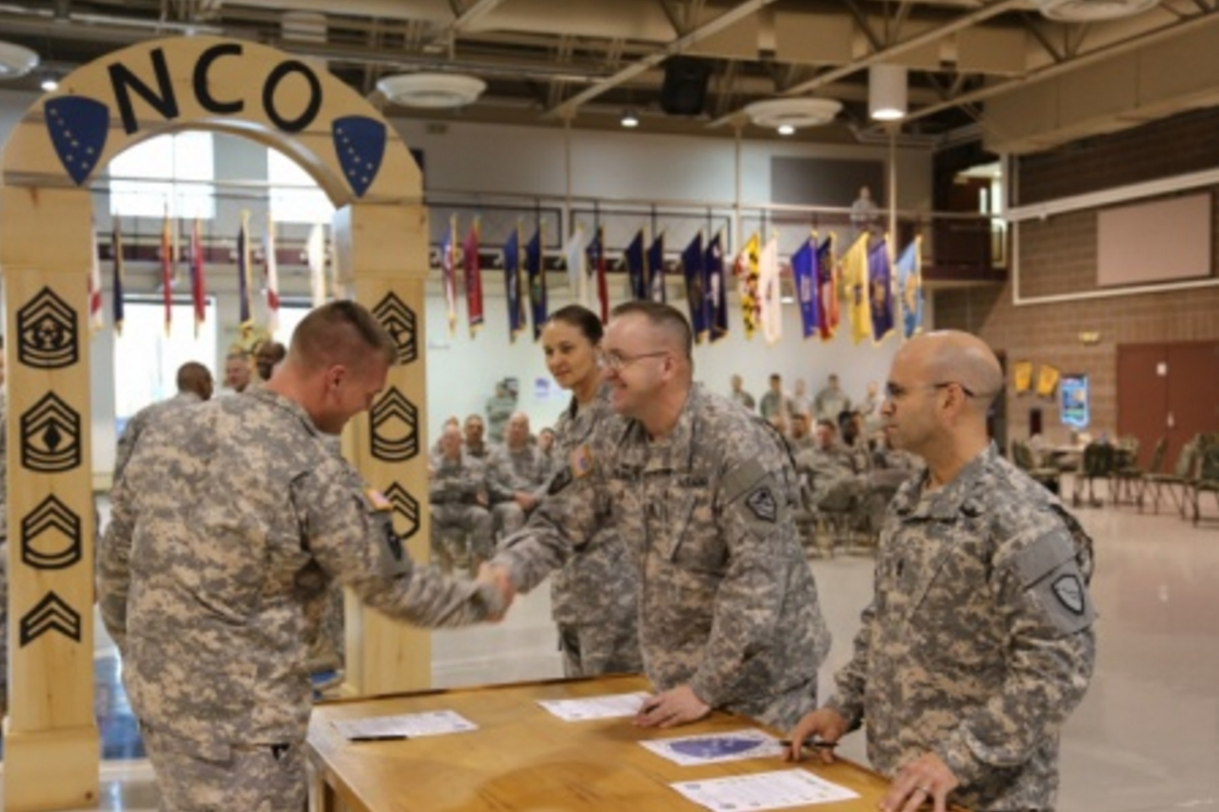 Command Sgt. Maj. Hildreth (second from right) shakes the hands of Sergeants attending the Non-Commissioned Officer's Professional Workshop as they were inducted into the NCO Corps during a ceremony held at the Alaska National Guard armory on Joint Base Elmendorf-Richardson