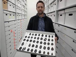 Archeologist Jeff Rasic holds a tray of obsidian tools found in the Nogahabara Dunes west of the Koyukuk River. Photo by Ned Rozell.  U.S. Fish and Wildlife Service biologist Karin Bodony at the site of an obsidian tool discovery in the Nogahabara Dunes in 2002. Photo by Dan Odess.