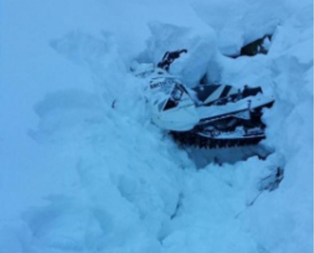 A snowmobile is buried in a snowbank after the operator becomes stranded near Dan Moeller Bowl on Douglas Island near Juneau, Alaska, Jan. 5, 2016. The man was located, hoisted and transported to Juneau by a Coast Guard Air Station Sitka MH-60 Jayhawk helicopter crew. U.S. Coast Guard photo.