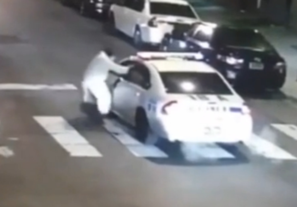 Gunman shown at the patrol car after firing as he approached. Image-Surveillance video