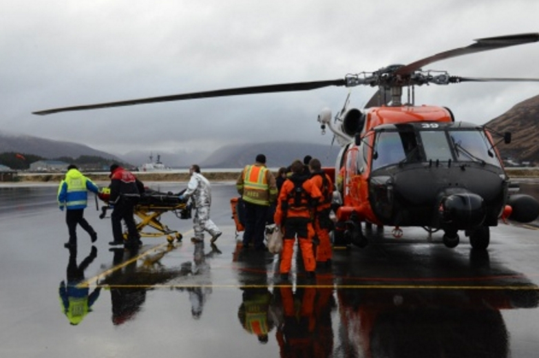An injured crewmember from the 728-foot cargo ship Cemtex Venture is transferred to awaiting emergency medical services personnel at Air Station Kodiak. (U.S. Coast Guard photo by Petty Officer 1st Class Kelly Parker)