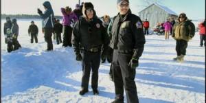 Alaska Wildlife troopers Darrell Hildebrand and Jon Simeon watch as Iron Dog participants leaveTanana. Image-DPS