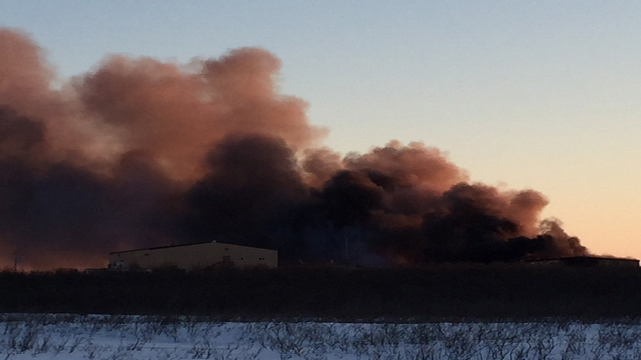 Smoke billows from the blaze that destroyed three Kwikpac buildings and two buildings belonging to Yukon Marine Manufacturing building over the weekend. Image-Alaska State Troopers
