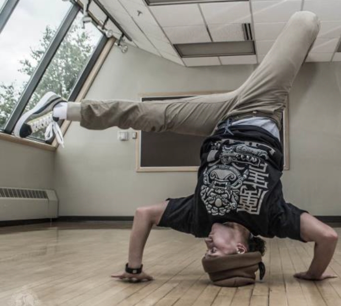 Alaska National Guardsman Sgt. Brianna McMillen, a UH-60 Black Hawk helicopter crew chief with 1st Battalion, 207th Aviation Regiment, breakdances at the Fairview Recreation Center in Anchorage, Alaska, July 23, 2015. (Photo courtesy of Darel Carey, LiHai Art)