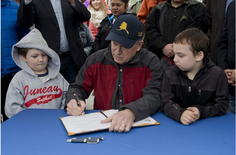 Alaska's Governor Walker signing  HB 128 into law at the Juneau Maritime Festival on Sunday. Image-State of Alaska