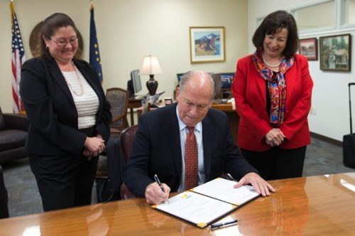 Governor Walker signing House Bill 234 while Representative Vazquez and a staffer look on. Image-State of Alaska