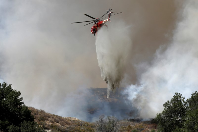 A firefighting helicopter makes a water drop at the so-called Sand Fire in the Angeles National Forest near Los Angeles, California, U.S. July 24, 2016. REUTERS/Jonathan Alcorn