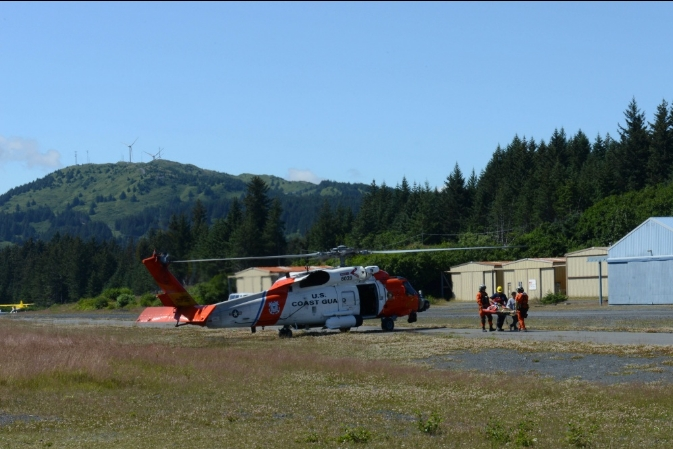 The crew of an MH-60 Jayhawk transfers the victim of the Chiniak Highway ATVV rollover to EMS at the Lilly Lake Seaplane Base in Kodiak. Image-Petty Officer 1st Class Kelly Parker | USCG