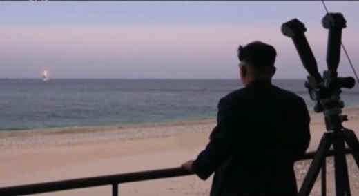 North Korea's Kim Jong Un observing launch of ballistic missile from submarine.