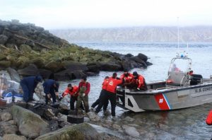 Crewmembers from the Coast Guard Cutter SPAR work alongside residents from the island of Little Diomede to load electronic waste onto SPAR's small boat to be properly disposed of on the mainland Aug. 25, 2016. Image-Petty Officer 1st Class Austen Shannon/USCG