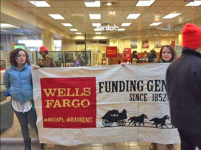 Protesters holding up a banner in front of Wells Fargo's 5th Avenue Mall branch in Anchorage Tuesday. Image-Alaska Rising Tide