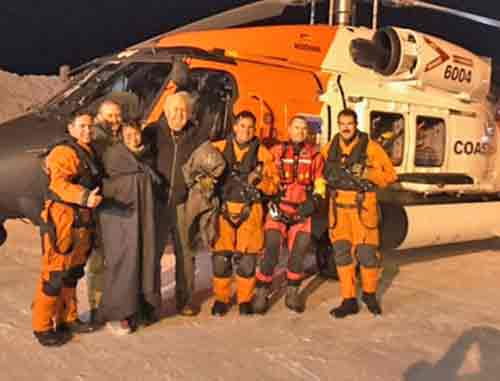 Three survivors aboard a downed Cessna 180 take a photo with the Coast Guard Air Station Kodiak MH-60T Jayhawk crew who rescued them. Photo by Petty Officer 1st Class William Colclough/USCG