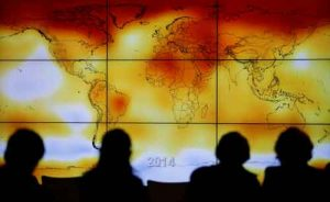 Participants seen in silhouette as they look at world map with climate anomalies. Image-Reuters/Stephane Mahe/File photo