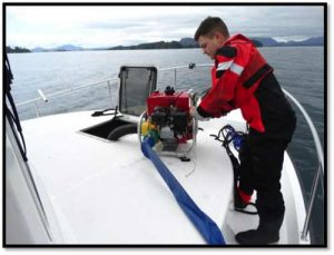 Petty Officer 2nd Class Derrick Depriest, a damage controlman on board the Coast Guard Cutter John McCormick, operates a P-6 pump to combat flooding in the forward living quarters of a tug that ran aground on the Vitskari Rocks, near Sitka. Image-USCG