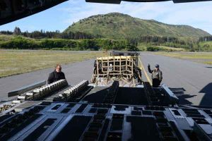Tech. Sgt. Tom Hough (right), a loadmaster assigned to the 249th Airlift Squadron with the Alaska Air National Guard, signals to raise a pallet of equipment and supplies to load onboard a C-17 Globemaster III cargo aircraft at Coast Guard Air Station Kodiak. U.S. Coast Guard photo by Petty Officer 1st Class Bill Colclough.
