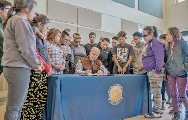 Governor Walker signing HB-141 allocating funds to the Alaska Technical and Vocational Education Program, in front of Bethel students. Image-State of Alaska