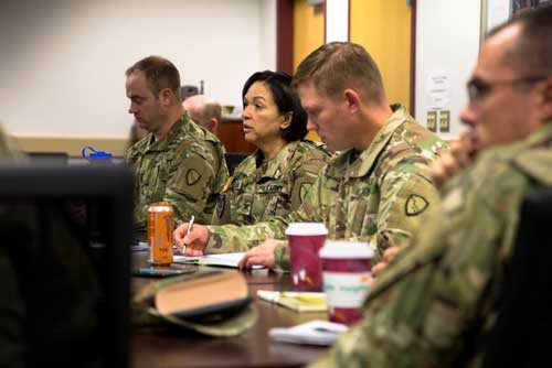 Members of the Alaska National Guard's Joint Operations Center, led by Col. Kimberely DeRouen (2nd from left), meet to finalize details for the deployment of more than 50 Soldiers to St. Croix, U.S. Virgin Islands at the Alaska National Guard armory, Joint Base Elmendorf-Richardson, Oct. 17. (Alaska Army National Guard photo by 2nd Lt. Marisa Lindsay/released)