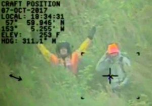 Helicopter crew signals chopper while with hunter on Raspberry Island in the Kodiak Archipelago. Image-USCG