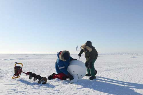 A research team deploys an ice beacon on sea ice north of Utqiagvik (formerly known as Barrow), Alaska's northernmost community. Photo by Ignatius Rigor of the Polar Science Center, Applied Physics Laboratory University of Washington.