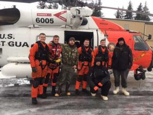A Coast Guard Air Station Kodiak MH-60 helicopter crew pose with three men they rescued from Chenega Island, Alaska, Jan. 1, 2018. Image-Lt Brian Dykens/USCG