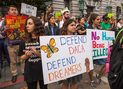 Protesters hold various signs and banners at a DACA rally in San Francisco. Image-Pax Ahimsa Gethen/Creative Commons