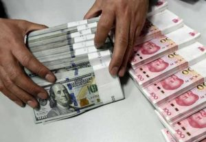 A clerk counts Chinese yuan and U.S. dollar banknotes at a branch of Bank of China