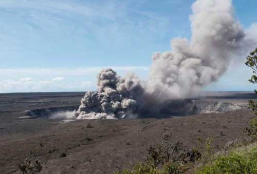In this May 11, 2018, photo released by the U.S. Geological Survey, a weak ash plume rises from the Overlook Vent in Halema'uma'u crater of the Kilauea volcano on the Big Island of Hawaii.