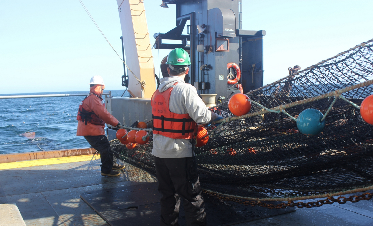 Crew members align the net as it winches in with the fish in the orange bag that still trails in the water. (Credit: NOAA)