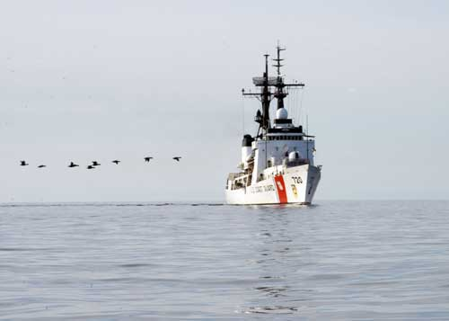 A line of birds crosses the bows of Coast Guard Cutter Sherman as crews return to the cutter in a small boat after conducting SAR and Kids Don't Float training in Wainwright, Alaska July 14, 2017. The cutter visited several Arctic villages as part of Operation Arctic Shield 2017. U.S. Coast Guard photo by Chief Petty Officer John Masson.