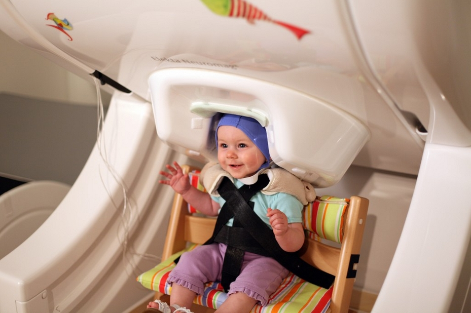 "A year-old baby sits in a brain scanner, called magnetoencephalography — a noninvasive approach to measuring brain activity. The baby listens to speech sounds like ""da"" and ""ta"" played over headphones while researchers record her brain responses. Image-Institute for Learning & Brain Sciences, UW"