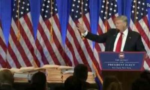 Donald Trump gesturing to manila files he says contain the transfer documents for his companies. Image-C-SPAN sccreengrab