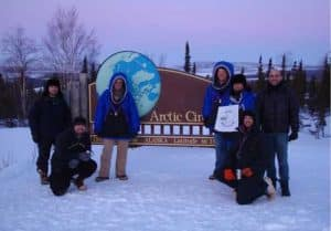 """From left, Ryan West, Shawn Freitas, John Whittington, Doug Morrow, Bernie Tao, Darrin Marshall, and Andy Soria pose at the Arctic Circle pull-out on the Dalton Highway, where they camped in March 2009 to test the cold-weather performance of """"Permaflo Biodiesel."""" Photo courtesy Darrin Marshall."""