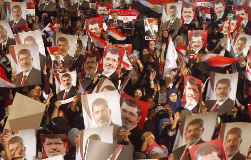 Members of the Muslim Brotherhood and supporters of Egypt's President Mohamed Mursi hold pictures of him. Image-VOA