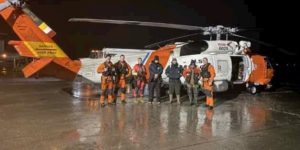 An MH-60 Jayhawk helicopter crew from Air Station Sitka, share a moment at the Juneau Airport with three boaters they rescued about an hour earlier. (U.S. Coast Guard photo by Coast Guard Air Station Sitka)