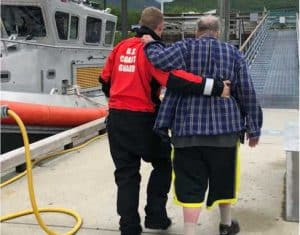 A Coast Guard Station Valdez crew member assists a 72-year-old man off the pier in Valdez, Alaska, after rescuing him from the 33-foot vessel Study Beauty. U.S. Coast Guard photo by Petty Officer 3rd Class Alexander Sheltra.